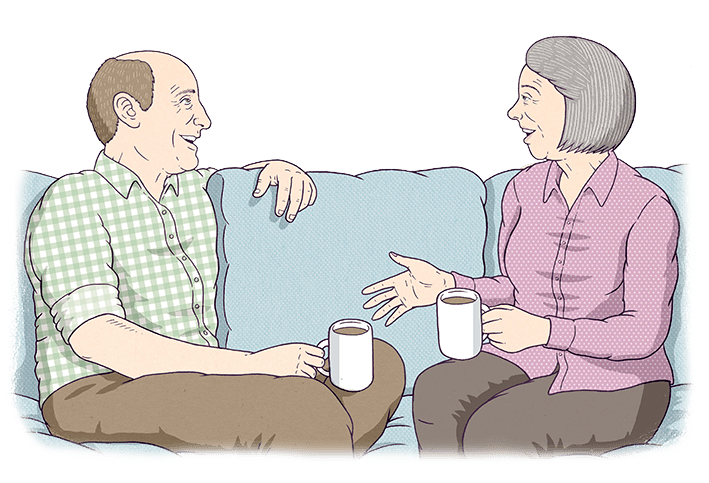 Two old people are sitting on a couch, talking.